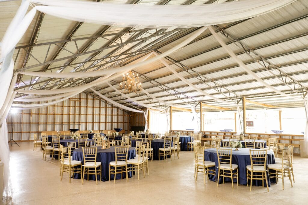 indoor modern barn wedding reception with white and blue decor